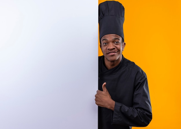 Junger lächelnder afroamerikanischer koch in der kochuniform steht hinter weißer wand und daumen hoch lokalisiert auf orange wand