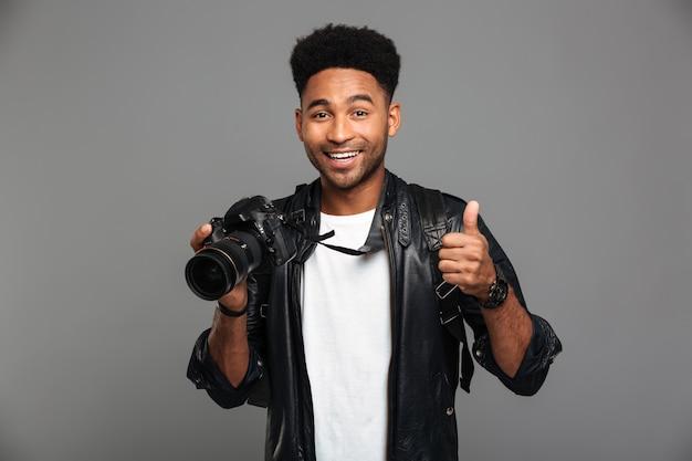 Junger lächelnder afroamerikanischer mann, der photocamera hält und den daumen herauf die geste, schauend zeigt