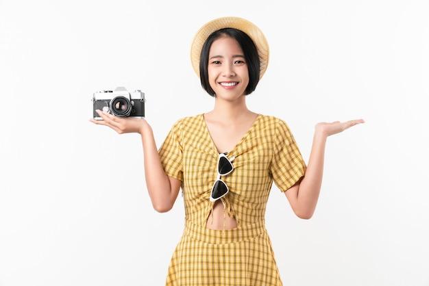 Junger lächelnder asiatischer frauentourist, der kamera hält und raum auf weißem hintergrund kopiert.