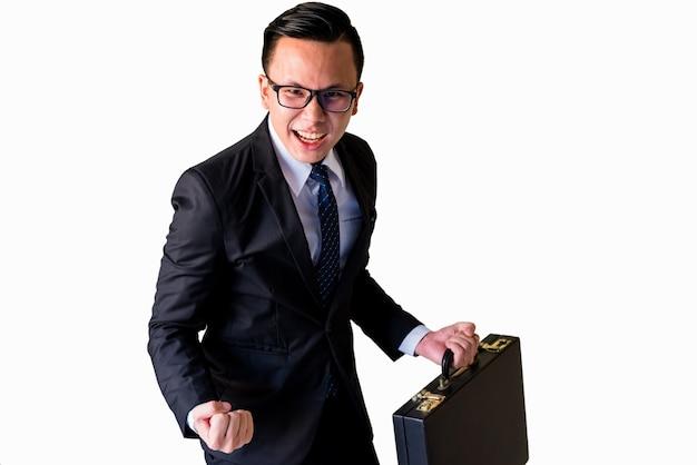 Junger lächelnder asiatischer geschäftsmann im schwarzen anzug und in den brillen, die mit dem gewinnerfolg lokalisiert auf weißem hintergrund stehen. feiern, aufmuntern oder erfolgskonzept.
