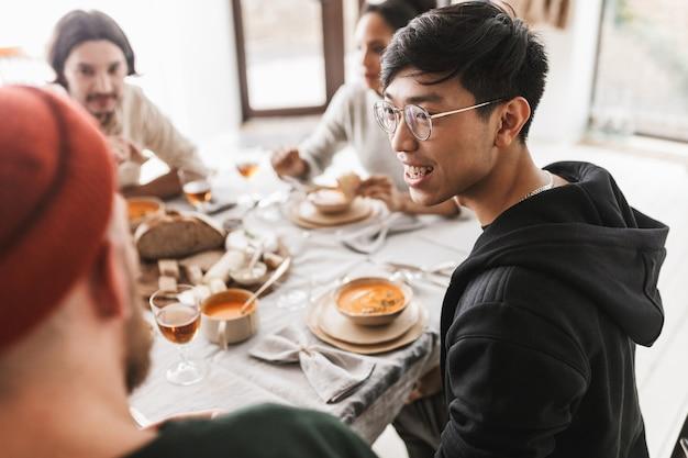 Junger lächelnder asiatischer mann mit dunklem haar in brille und kapuzenpulli, die glücklich am tisch sitzen