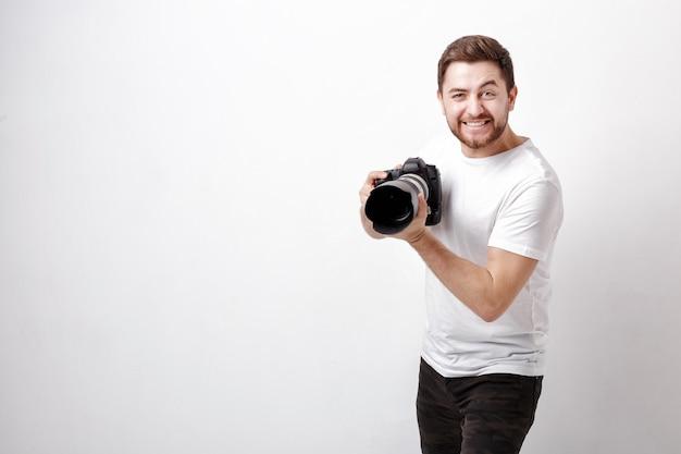 Junger lächelnder berufsfotograf im weißen t-shirt verwendet eine digitalkamera mit einem langen objektiv