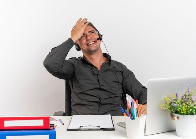 Junger lächelnder blonder büroangestelltermann auf kopfhörern sitzt am schreibtisch mit bürowerkzeugen unter verwendung des laptops setzt hand auf kopf, der lokalisiert auf weißem hintergrund mit kopienraum sucht