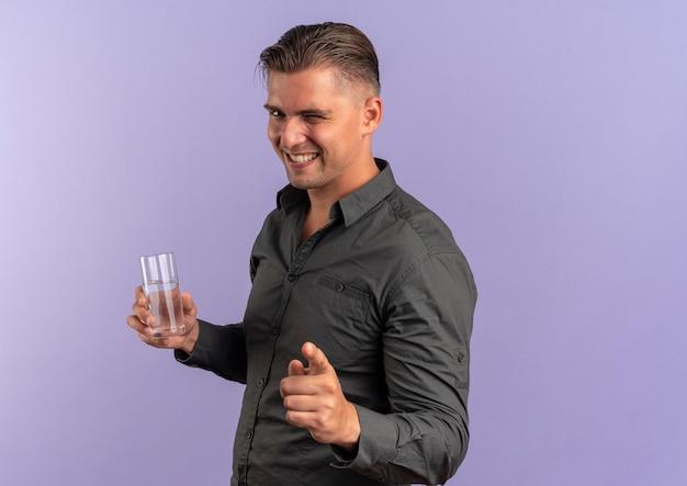 Junger lächelnder blonder hübscher mann blinkt auge und zeigt auf kamera, die glas wasser lokalisiert auf violettem hintergrund mit kopienraum hält