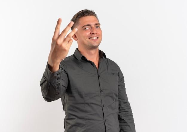 Junger lächelnder blonder hübscher mann gestikuliert drei mit den fingern lokalisiert auf weißem hintergrund mit kopienraum