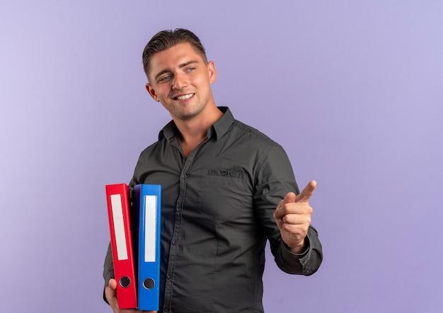 Junger lächelnder blonder hübscher mann hält aktenordner, die auf seite schauen und auf violetten raum mit kopierraum isoliert zeigen