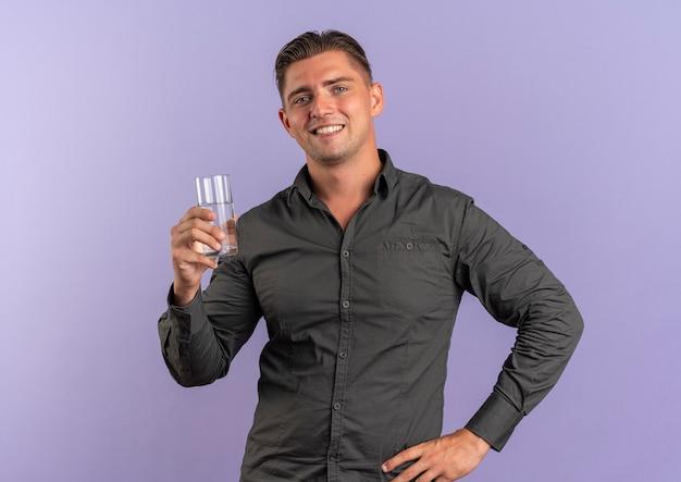 Junger lächelnder blonder hübscher mann hält glas wasser lokalisiert auf violettem raum mit kopienraum