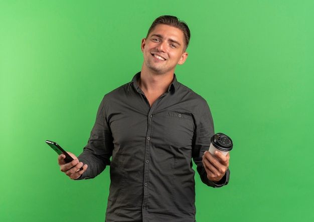 Junger lächelnder blonder hübscher mann hält telefon und kaffeetasse lokalisiert auf grünfläche mit kopienraum