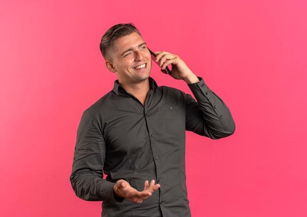 Junger lächelnder blonder hübscher mann spricht am telefon, das die seite lokalisiert auf rosa raum mit kopienraum betrachtet