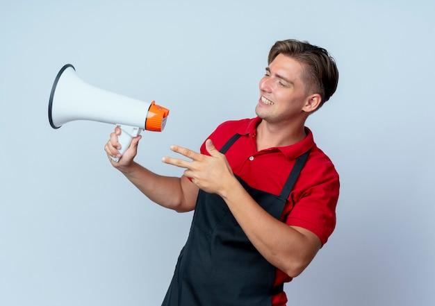 Junger lächelnder blonder männlicher friseur in der uniform hält lautsprecher, der seite lokalisiert auf weißem hintergrund mit kopienraum betrachtet