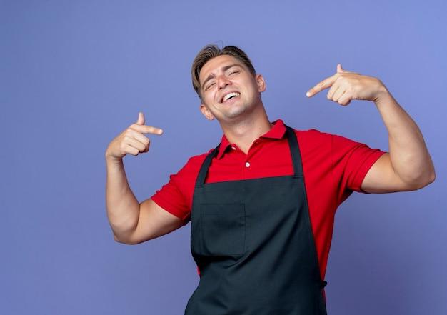Junger lächelnder blonder männlicher friseur in uniform zeigt auf sich selbst isoliert auf violettem raum mit kopienraum