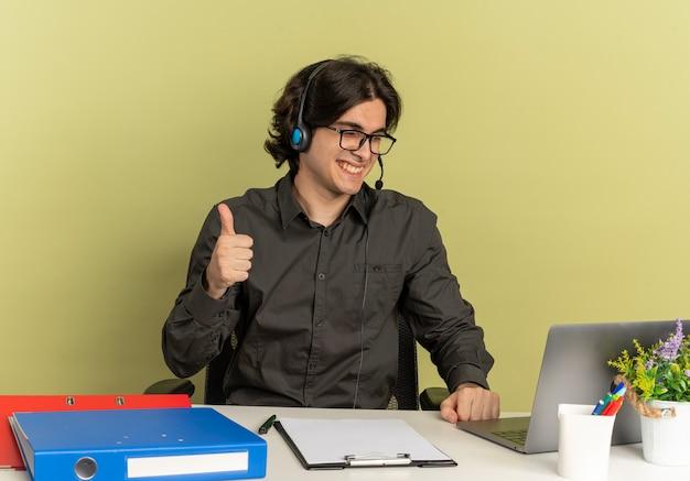 Junger lächelnder büroangestelltermann auf kopfhörern in optischen gläsern sitzt am schreibtisch mit bürowerkzeugen, die laptop-daumen hoch verwenden und betrachten