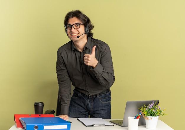Junger lächelnder büroangestelltermann auf kopfhörern in optischen gläsern steht am schreibtisch mit bürowerkzeugen unter verwendung der laptop-daumen hoch lokalisiert auf grünem hintergrund mit kopienraum