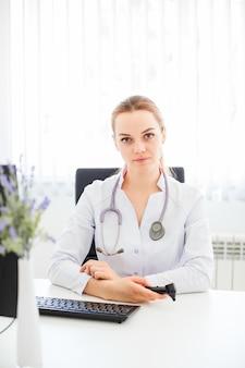 Junger lächelnder doktor, der am schreibtisch auf einem schwarzen stuhl mit ihren armen gekreuzt sitzt