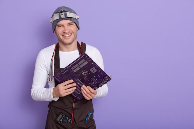 Junger lächelnder elektriker nach überprüfung der gebrauchstauglichkeit des motherboards
