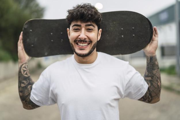 Junger lächelnder europäischer cooler mann, der einen schlittschuh auf unscharfer straße hält