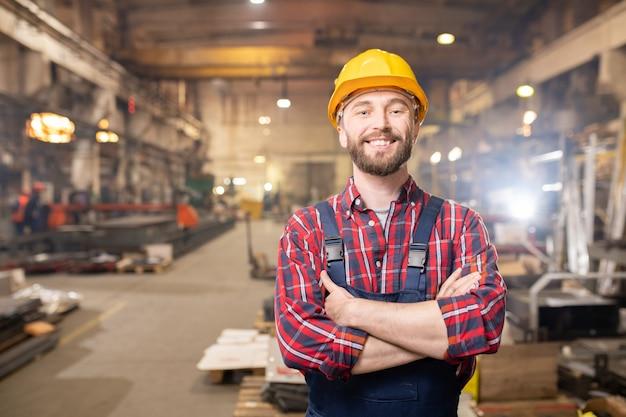 Junger lächelnder fachmann in overalls und schutzhelm, der innerhalb des großen industriewerks aufwirft