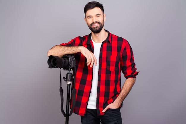 Junger lächelnder fotograf im roten hemd mit professioneller kamera