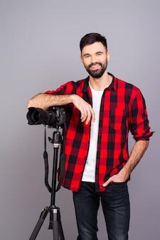 Junger lächelnder fotograf mit kamera auf grau