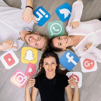 Junger lächelnder freund, der auf boden mit den social media-logos zeigt daumenzeichen liegt