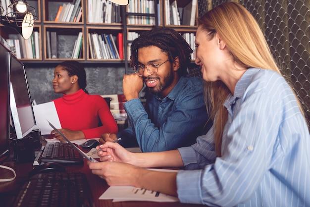 Junger lächelnder geschäftsmann und -frau, die zusammen im büro arbeiten und die erzielten positiven ergebnisse analysieren