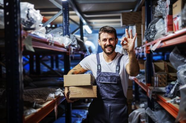 Junger lächelnder glücklicher bärtiger tätowierter fleißiger mitarbeiter, der kisten hält und im lager der import- und exportfirma steht und okay geste zeigt