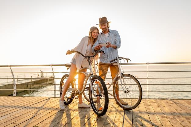 Junger lächelnder glücklicher mann und frau, die auf fahrrädern mit smartphone reisen