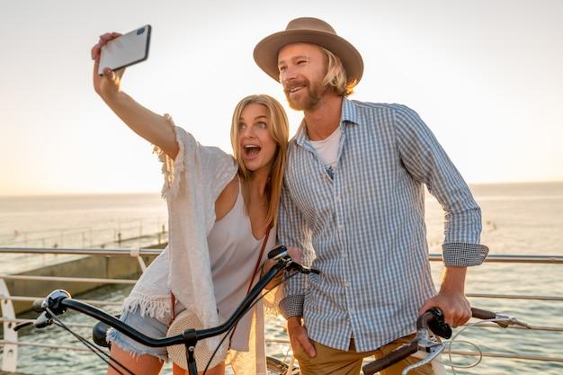 Junger lächelnder glücklicher mann und frau, die auf fahrrädern reisen, die selfie-foto auf telefonkamera machen