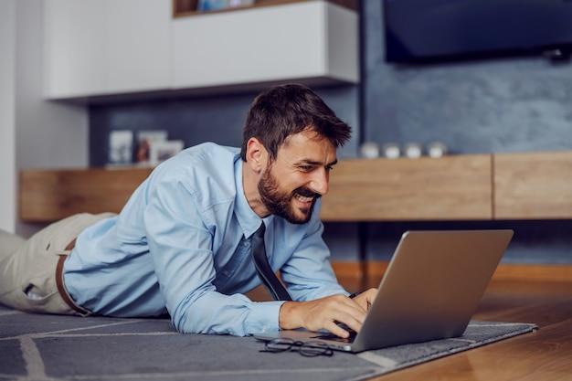 Junger lächelnder hübscher geschäftsmann, der auf bauch auf dem boden liegt und laptop verwendet.