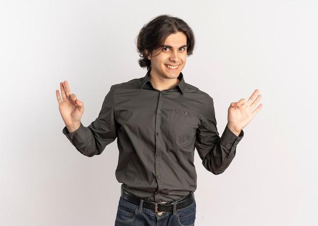 Junger lächelnder hübscher kaukasischer mann gestikuliert ok handzeichen lokalisiert auf weißem hintergrund mit kopienraum