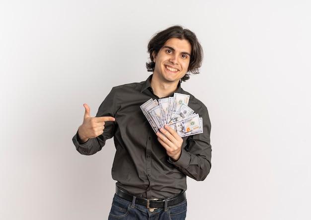 Junger lächelnder hübscher kaukasischer mann hält und zeigt auf geld