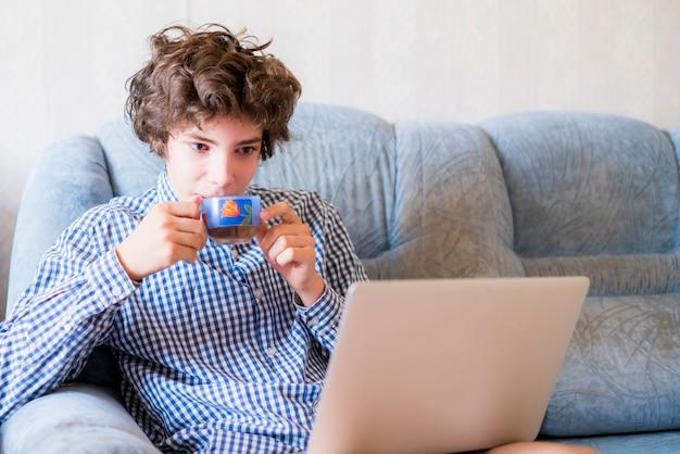 Junger lächelnder jugendlicher mit dem langen haar zu hause studierend unter verwendung des laptops, der auf einem sofa sitzt