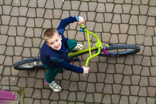 Junger lächelnder junge, der fahrrad am kühlen frühlingstag aufwärts schaut fährt