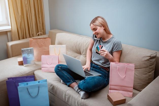 Junger lächelnder käufer mit laptop und kreditkarten bestellt per smartphone im online-shop, während er auf einem sofa mit einkaufstüten sitzt
