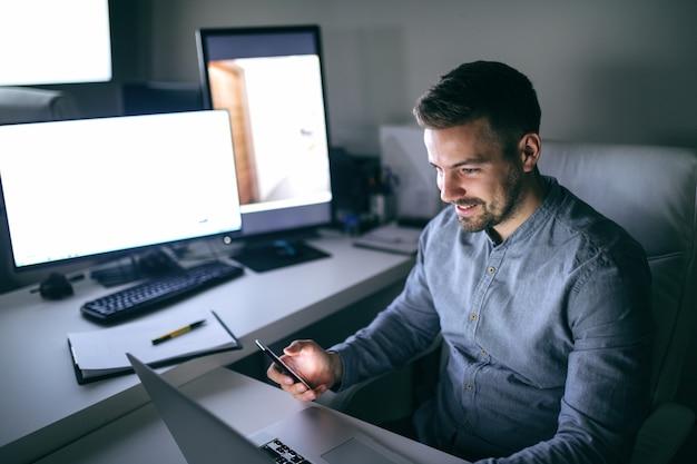 Junger lächelnder kaukasischer arbeiter, der computermonitor betrachtet und in der anderen hand smartphone hält, während im büro spät in der nacht sitzt. nachtarbeitskonzept.