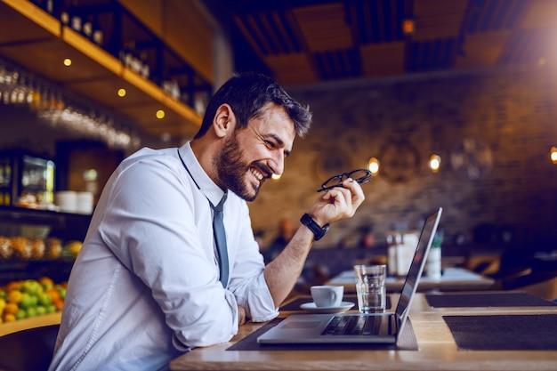 Junger lächelnder kaukasischer bärtiger café-manager, der am tisch sitzt und sich für gehaltserhöhung in diesem monat zufrieden fühlt.