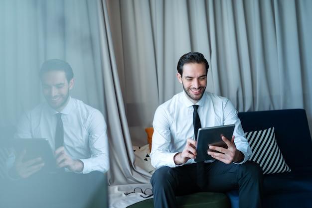 Junger lächelnder kaukasischer geschäftsmann in der formellen abnutzung, die tablette für arbeit und auf sofa im büro sitzend verwendet.
