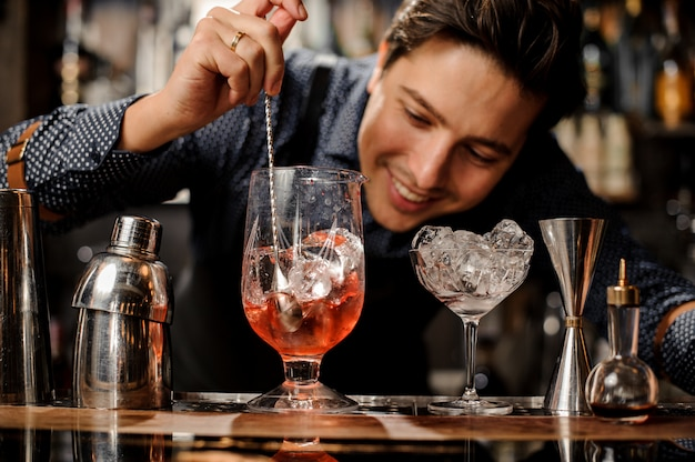 Junger lächelnder kellner, der frisches alkoholisches cocktail mit sirup rührt