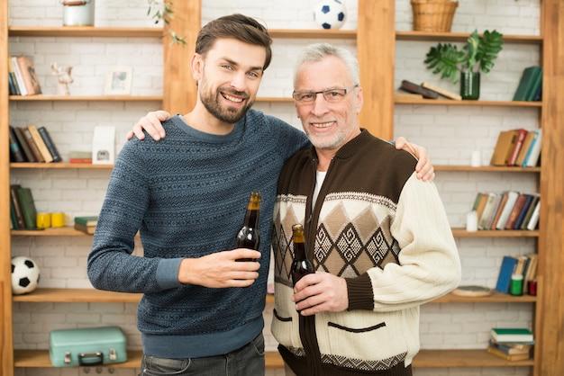 Junger lächelnder kerl, der mit gealtertem glücklichem mann mit flaschen umarmt
