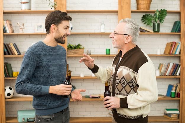 Junger lächelnder kerl, der mit gealtertem mann mit flaschen spricht