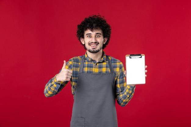 Junger lächelnder kerl-server mit lockigem haar, der die bestellung aufnimmt und eine ok geste auf isoliertem rotem hintergrund macht