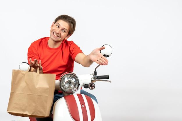 Junger lächelnder lieferbote in der roten uniform, die auf roller sitzt, der papiertüte hält und auf weißer wand begrüßt