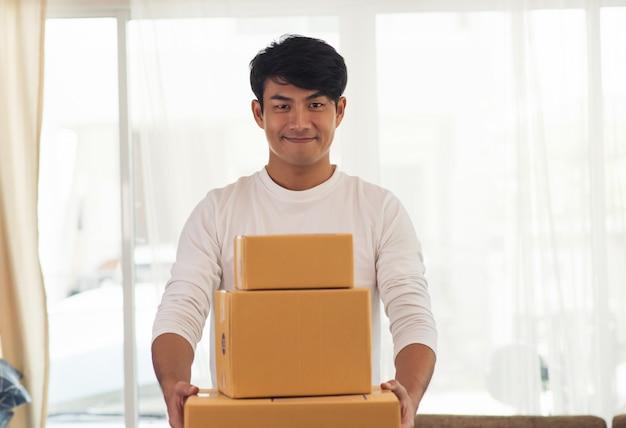 Junger lächelnder logistischer lieferer, der den kasten hält