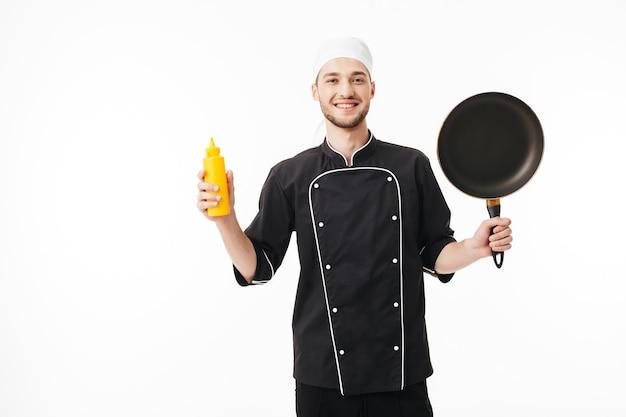 Junger lächelnder männlicher koch in der schwarzen uniform, die pfanne und flasche senf in den händen hält, während glücklich