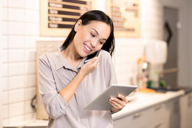 Junger lächelnder manager des luxuriösen restaurants, der durch online-menü im tablett blättert, während er einen der kunden am telefon konsultiert