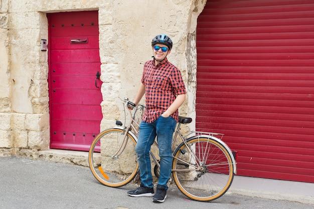 Junger lächelnder mann am helm, rotes hemd und sonnenbrille halten fahrrad auf der außenseite.