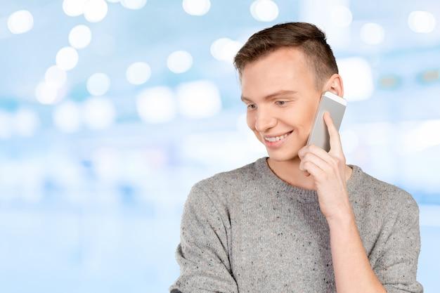 Junger lächelnder mann, der am handy spricht