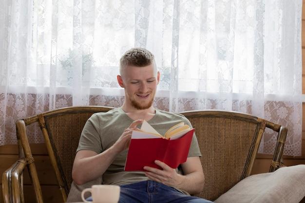 Junger lächelnder mann, der buch mit roter abdeckung auf weidenbank im ländlichen holzhaus liest