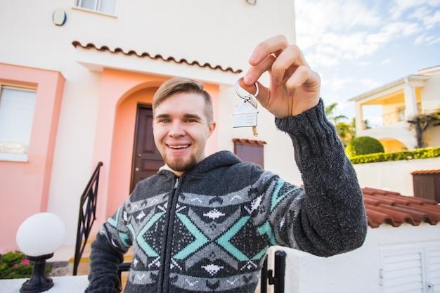 Junger lächelnder mann, der den schlüssel zum neuen hauskonzept des wohnungsmieters und des neuen zuhauses zeigt