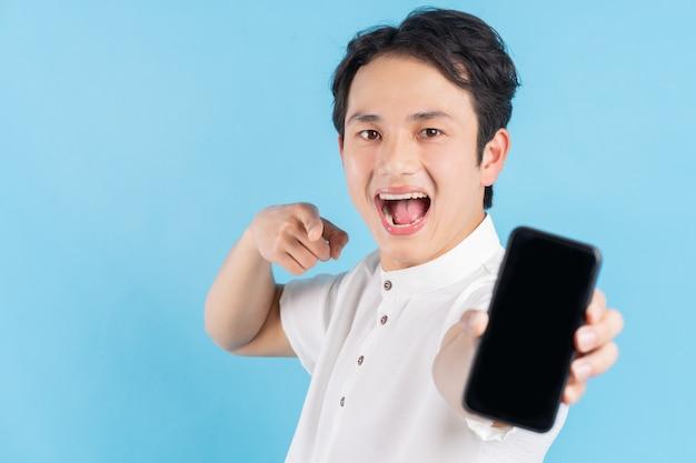 Junger lächelnder mann, der ein modernes smartphone in seiner hand hält und seinen finger auf leeren weißen bildschirm, auf blau zeigt.